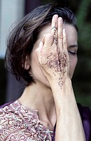 Darkhaired Woman in a Saree holding one with Henna painted Hand over her Eye _ Meditation _ Tradition