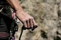 Male hand with a carabiner on a rope in front of a rocky wall, close_up, selective focus