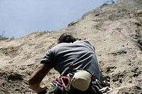 Young man with black hair climbing up a rocky wall, selective focus
