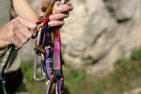 Young man is holding up a medium group of carabiners, selective focus