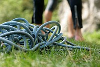 Climbing rope lying on the ground in front of a person part of, selective focus