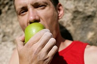 Young man in front of a rock face biting into an apple, selective focus
