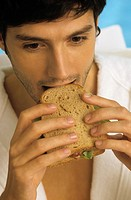 Darkhaired Man in a Bathrobe biting into a Sandwich _ Snack _ Foodstuff