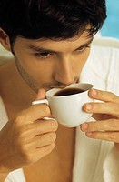 Darkhaired Man in a Bathrobe drinking from a Coffee_Cup _ Look _ Hot Beverage _ Leisure Time