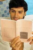 Darkhaired Man in a Bath Robe reading a Book _ Wellness _ Leisure Time _ Print Media