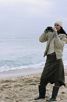 Young brownhaired Woman with woolen Hat and Rubber Boots looking through Binoculars _ View _ Leisure Time _ Coldness _ Beach
