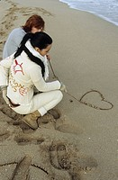 Young Man with auburn Hair drawing a Heart into the Sand with a Stick - Symbol - Love -... (thumbnail)