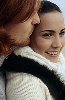 Young darkhaired Woman leaning against the Chest of an auburn haired Man _ Togetherness _ Relationship _ Tenderness