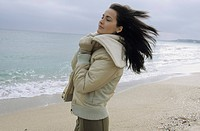 Young darkhaired Woman cuddling herself into the Collar of her winterly Jacket _ Wind _ Season _ Gesture _ Beach