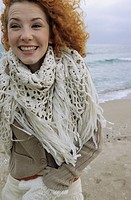 Young Woman with strawberry_blonde Hair carrying a fringy Scarf around her Neck and is grinning _ Fun _ Happiness _ Beach