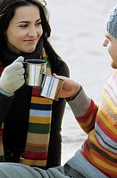 Young Couple clinking Glasses with metallic Cups _ Gesture _ Hot Beverage _ Season _ Beach