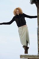Young redhaired Woman balancing on the Terrace of a wooden Cottage _ Fun _ Leisure Time