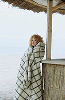 Young redhaired Woman leaning against a Beach_Bar _ Coldness _ Season
