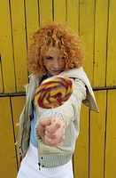 Young redhaired Woman elongating a Lollipop in the Face of the Spectator _ Facial Expression _ Allurement _ Sweets