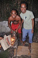 Dili (East Timor): two guys roasting a pork along the street, in the Leicidere neighborhood