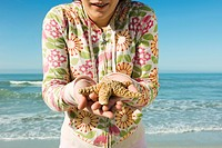 Teen girl holding starfish at the beach, cropped