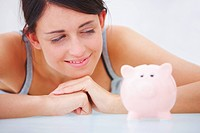 Closeup of a happy young lady looking at piggybank