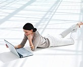 Full length of a young Woman lying on floor using laptop