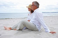 Full length of romantic old couple sitting together on beach
