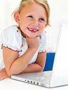 Closeup portrait of a smiling girl sitting by laptop