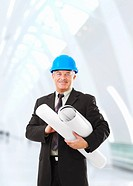 Senior construction worker with helmet and blueprints