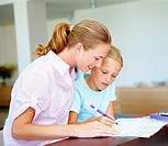 Caring mother helping her daughter with homework