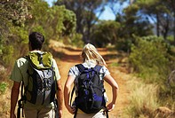 Rear view of a young couple carrying backpacks and walking through a forest