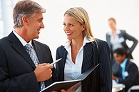 Business signing a file while speaking to his secretary
