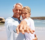 Retired couple having fun the sea shore on a funny day