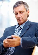 Mature business man using his mobile to text message