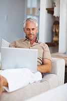 Handsome retired man working on a laptop at home