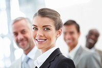 Blur image of a cheerful business woman in front with her staff standing behind