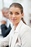 Portrait of a lovely smiling business woman with people in the background