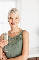 Portrait of a happy old woman holding a glass of champagne