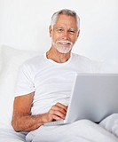 Portrait of senior retired happy man with a laptop