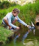 Portrait of a young boy playing with a toy boat at a pond