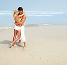 Full length of a young couple hugging each other at the beach