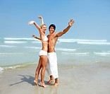 Portarit of an excited young couple having a great time at the beach
