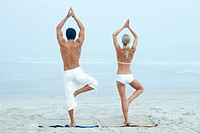 Rear view of a man and woman practicing yoga at the beach