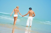Portrait of a young couple holding hands and walking on the beach