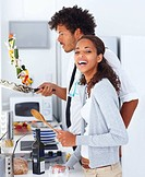 Portrait of a happy young couple preparing food together at home