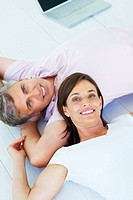 Portrait of a happy mature couple lying down together at their home