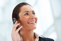 Closeup portrait of young confident business woman smiling and speaking on mobile
