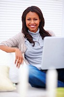 Smiling young woman sitting comfortably at home with a laptop