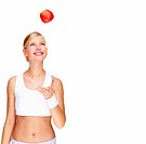 Smiling young woman tossing an apple over white background