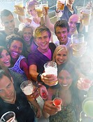Closeup portrait of young men and women holding drinks at a party