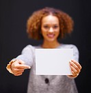 Young African American woman pointing on a blank white piece of paper