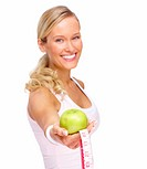 Young beautiful dietician offering apple and measuring tape over white background