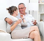 Loving older couple sitting together on couch at home
