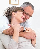 Smiling romantic couple hugging at home
